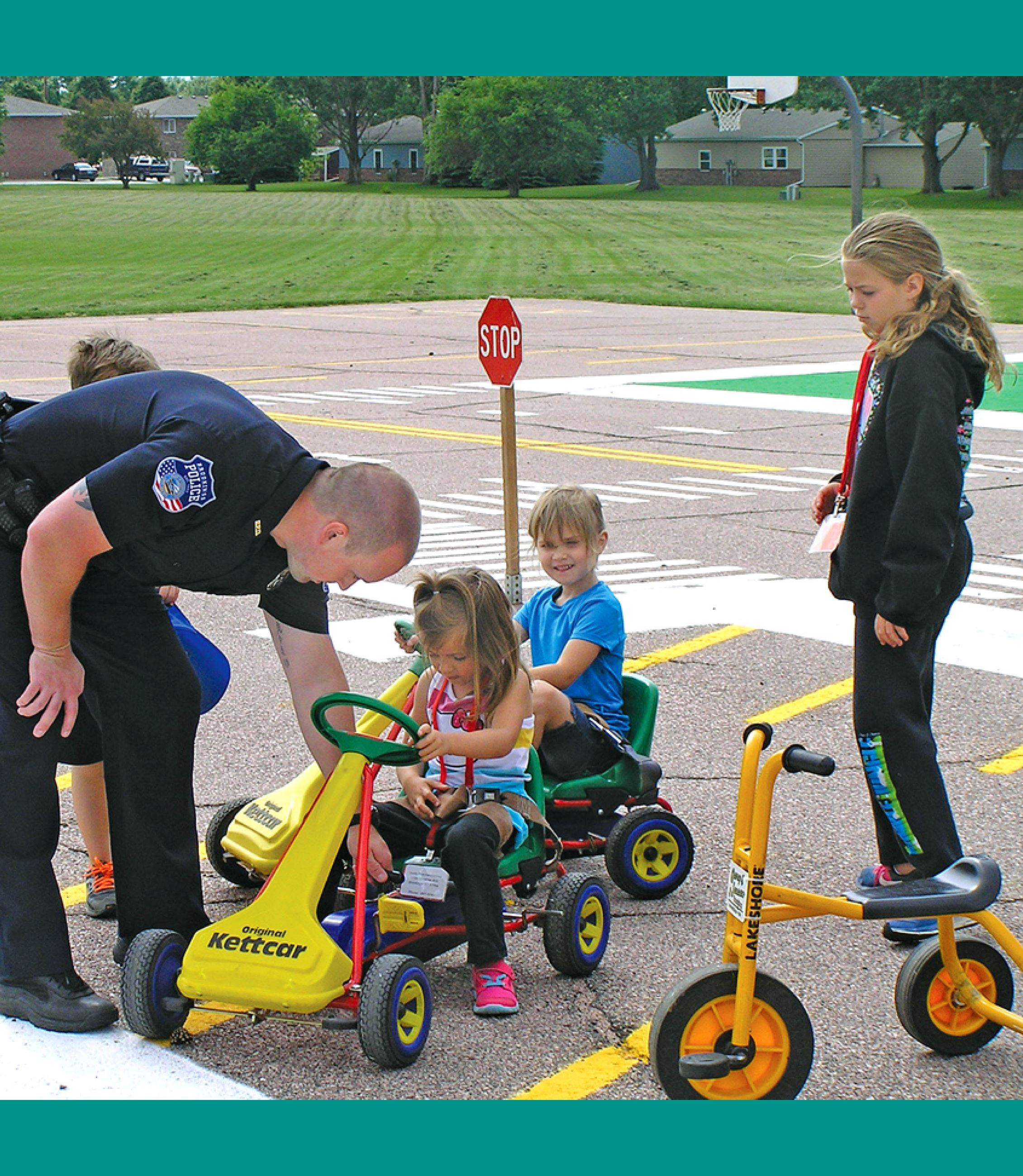 A police officer teaches children who are in peddle cars at safety town