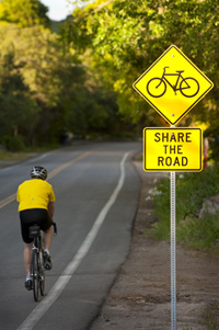 Man bicycling along Share the Road sign